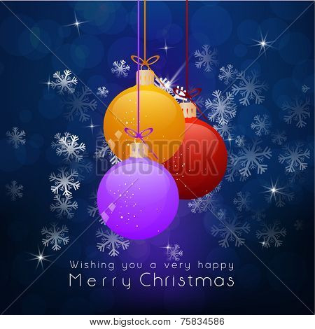 Merry Christmas celebration with colorful X-mas balls hanging on snowflakes decorated blue background.