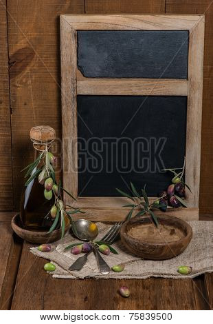 Olive Table Setting With Wooden Bowls, Gray Textile Napkin And Branch Of Olive On Old Wooden Table