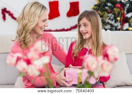 Little girl giving her mother a christmas gift at home in the living room