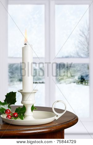 Christmas candle decorated with holly and berries against a winter window snow scene