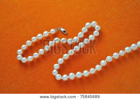 pearl necklace in orange velvet seamless abstract background