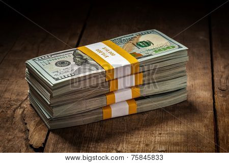 Creative business finance making money concept - stacks of new 100 US dollars 2013 edition banknotes (bills) bundles isolated on wooden background