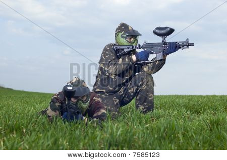 Two Men In Camouflage In Shelter From Logs, Playing In Paintballing