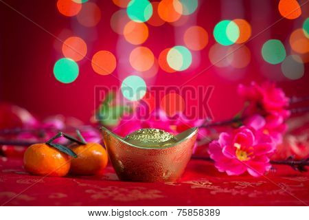 Chinese new year decorations, gold ingot on red glitter background.