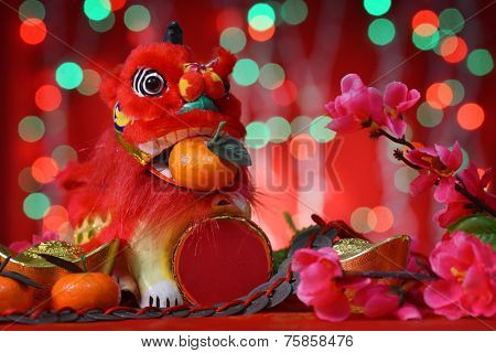 Chinese new year festival decorations, miniature dancing lion and mandarin orange, on glitter red background.