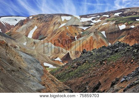 National Park Landmannalaugar in Iceland. Pieces of gray and black lava, sometimes covered with green moss. In the background - orange rhyolite mountains with last year's snow in the hollows