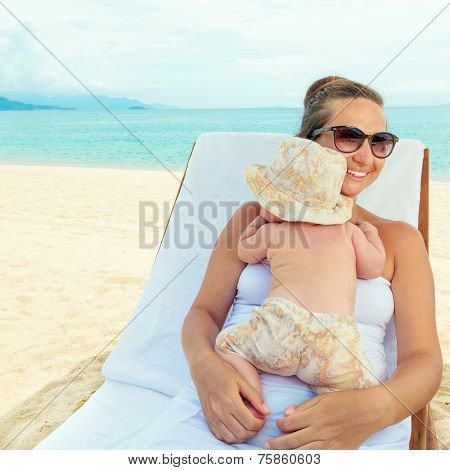 Baby and mom are relaxing on sunbed