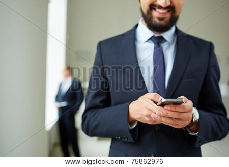 Close-up of young businessman using cellular phone on background of his colleague