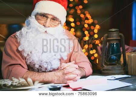 Senior man in Santa cap and beard looking at camera