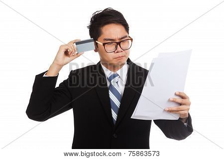 Asian Businessman Think With A Credit Card And  Statement