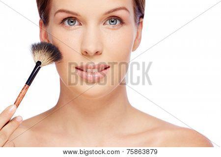 Pretty woman with powder brush looking at camera