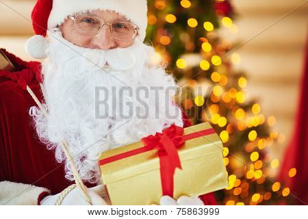 Portrait of happy Santa Claus holding golden giftbox tied by red ribbon