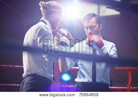 Elegant businessman in formalwear and boxing gloves looking at his rival before attack