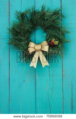 Christmas wreath with gold bow hanging on antique teal blue wooden background