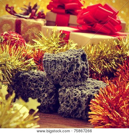some lumps of candy coal and some christmas ornaments and gifts on a rustic wooden table, with a retro effect
