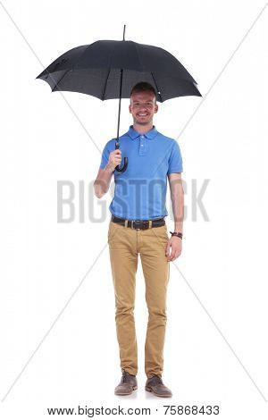 full length portrait of a young casual man holding a black umbrella and smiling for the camera. isolated on a white background