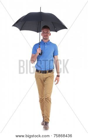 full length picture of a young casual man holding a black umbrella over his head and walking toward the camera. isolated on a white background