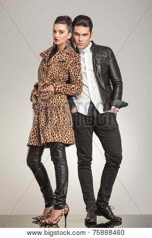 Fashion couple looking at the camera while holding their hands in pockets, ful body image.