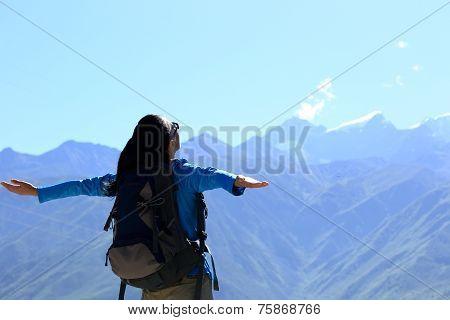cheering hiking woman enjoy the beautiful view at mountain peak in tibet,china