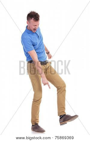 full length picture of a young casual man pointing angrily at the ground while holding his foot raised, on the point of stepping on something. isolated on a white background