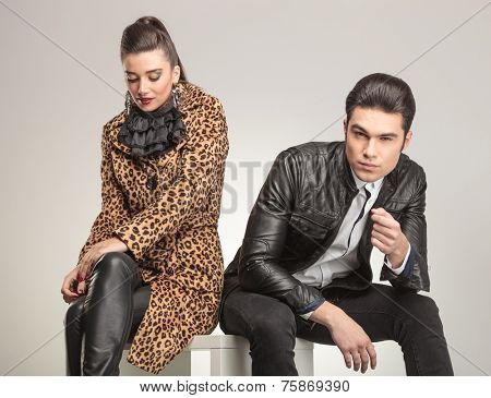 Beautiful fashion woman sitting and looking down while her lover is sitting and looking at the camera.