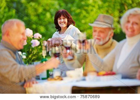 Happy senior people celebrating birthday with wine and cake in a garden