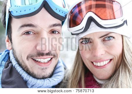 Happy woman in winter with ski goggles on a ski trip holding poles