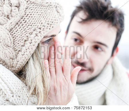 Woman crying near man in winter and wiping tear off her face