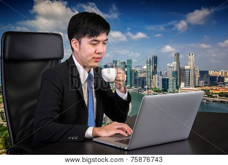 Portrait Of Goodlooking Asian Man Sitting At Table At Working Office With Laptop Computer