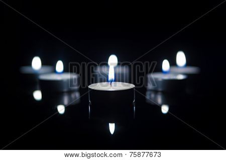 Tea Candles with Reflection on Black. Cold light