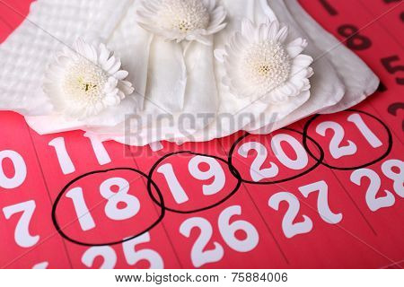 Sanitary pads and white flowers on red calendar background