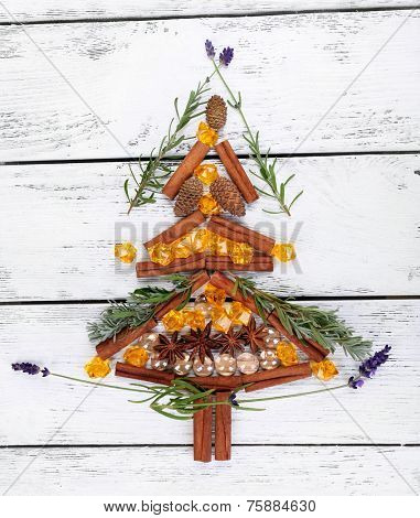 Christmas tree from acorns, cones and cinnamon on wooden background