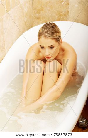 Nude woman sitting in a bath and thinking about some trouble.