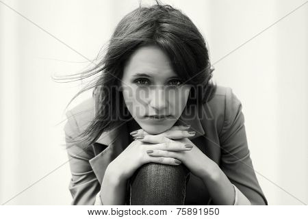 Sad young fashion woman against a white wall