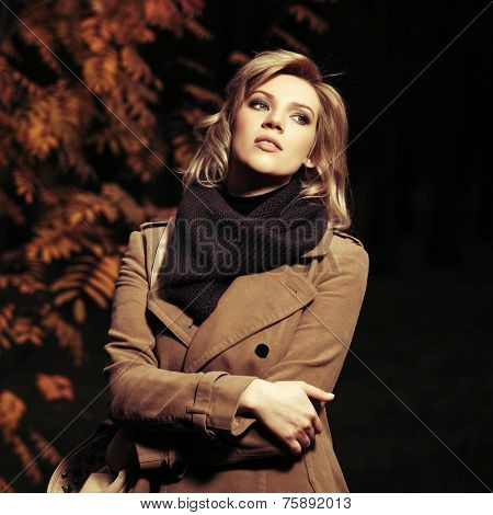 Young blond fashion woman walking in a night autumn forest