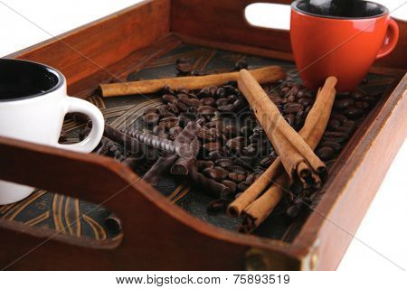 cinnamon sticks with coffee beans served on wooden tray isolated on white background