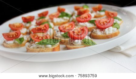 italian bruschetta with cherry tomato,basil and cheese on white plate