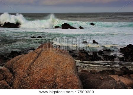 Closeup Of Rocks While Waves Crash In The Background