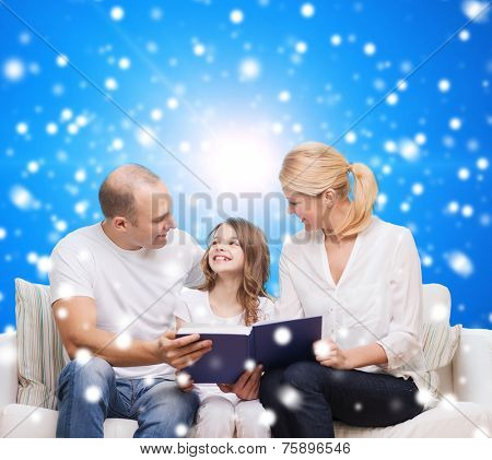 family, childhood, christmas holidays and people - smiling mother, father and little girl reading book over blue snowy background