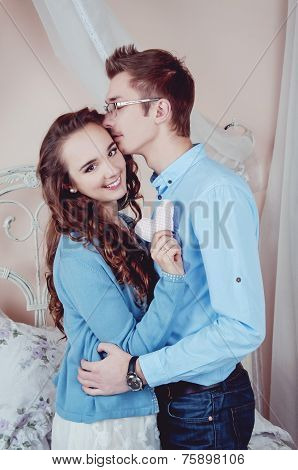 Young Loving Couple In The Bedroom