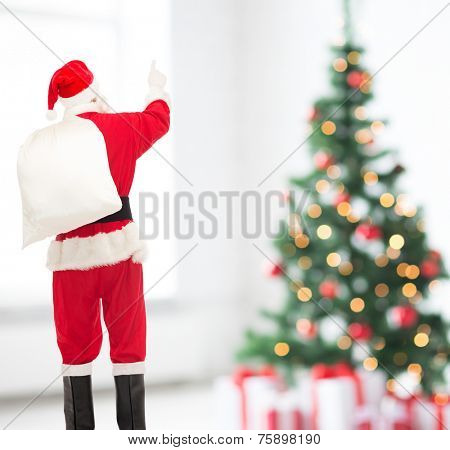 christmas, holidays and people concept - man in costume of santa claus with bag pointing finger from back over yellow lights background over living room and tree background