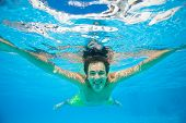 stock photo of crystal clear  - View of young happy smiling man swimming alone under the crystal - JPG