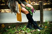 stock photo of woman boots  -  woman sit in park on wooden fence wearing leather boots - JPG