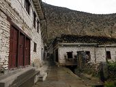 stock photo of mustang  - The old village of Marpha in the Annapurna Himalayas of Mustang Nepal during monsoon featuring typical white houses with wooden logs as roofs - JPG