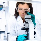 stock photo of microscope slide  - Attractive young PhD student scientist looking at the microscope slide in the life science research laboratory - JPG