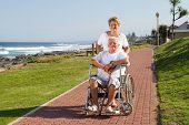 Постер, плакат: Счастливый старшая жена толкая пожилой муж в коляске