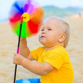 stock photo of laughable  - Baby playing with toy windmill - JPG