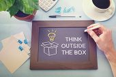stock photo of thinking outside box  - Man drawing Think Outside the Box with idea light bulb on a little blackboard - JPG
