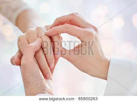 people, homosexuality, same-sex marriage and love concept - close up of happy lesbian couple hands putting on wedding ring over holiday lights background