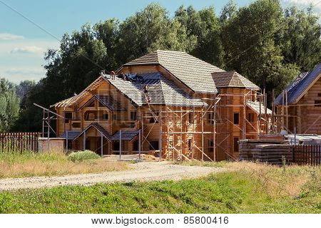 Builders Cover The Roof Of A Log House